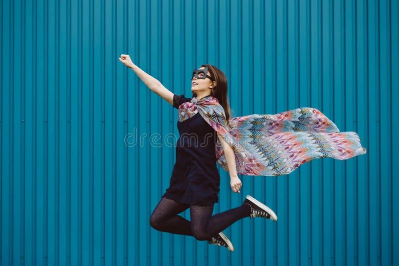 Girl in black superhero mask. Flying royalty free stock images
