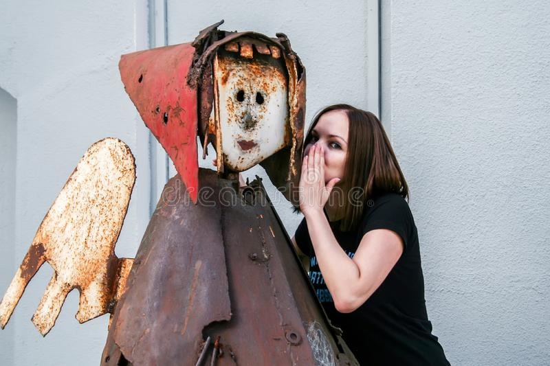 A girl in a black T-shirt whispers secrets to the ear of a metal statue of an angel royalty free stock images