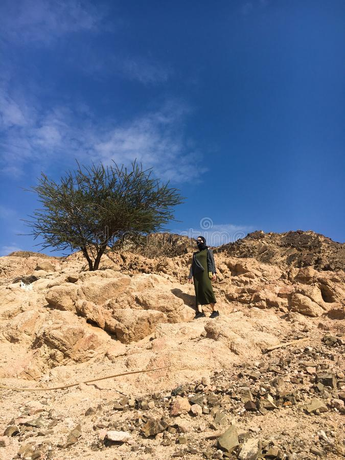The girl in the black veil climbs the mountain. Jordan, Aqaba royalty free stock photos