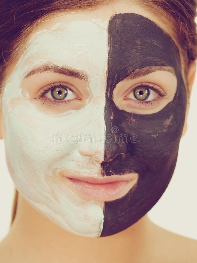 Girl with black white mud mask on face. Woman with clay carbo black mask on half face and white mud on second half. Girl taking care of oily complexion. Beauty royalty free stock photos