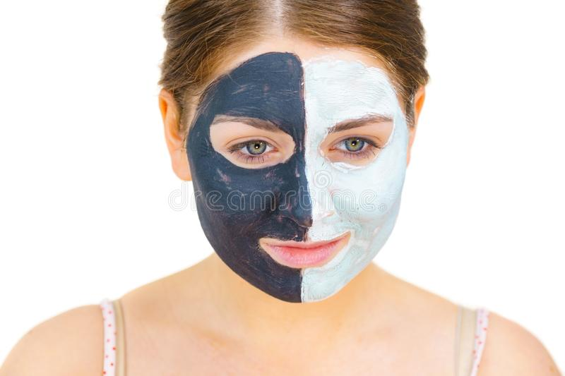 Girl with black white mud mask on face. Woman with clay carbo black mask on half face and white mud on second half. Girl taking care of oily complexion. Beauty royalty free stock photo