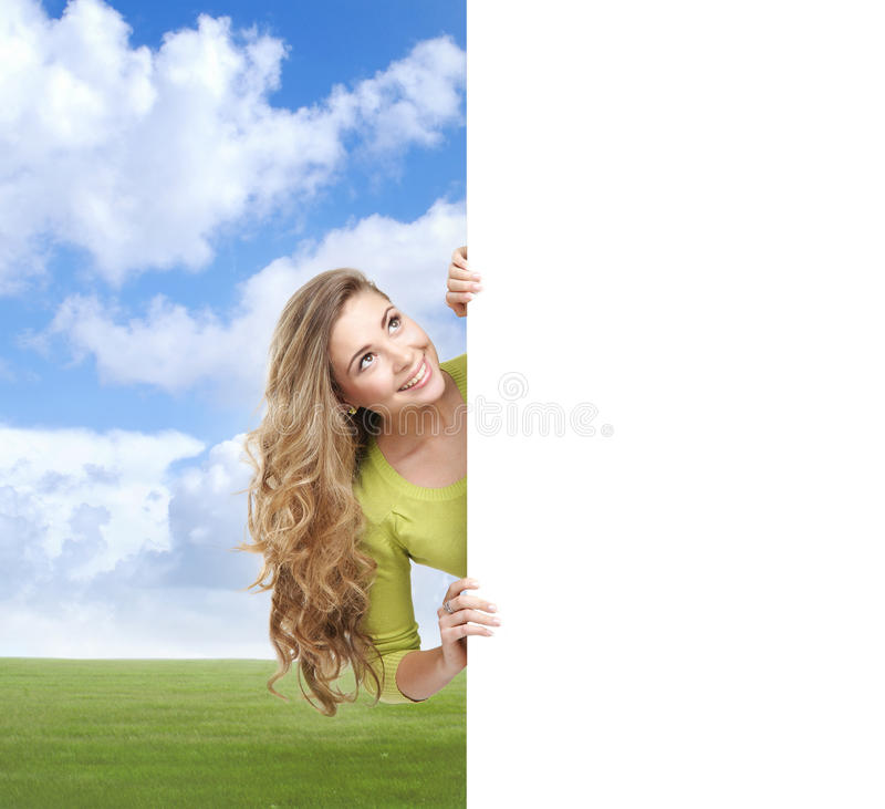 Girl with a blank banner. Perfect space to put any text. Girl with the blank banner over summer background. Perfect space to put any text stock photography