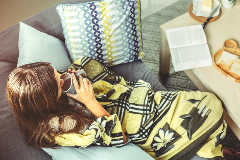 Girl in blanket relaxing on couch in living room. Young girl wrapped in blanket relaxing on a couch in living room. Comfortable weekend morning, top view stock photos