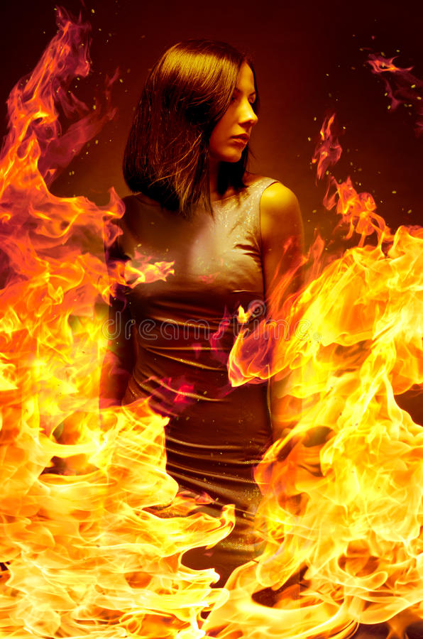 Girl is in blazing flame. Young beautiful girl is in blazing flame stock photo
