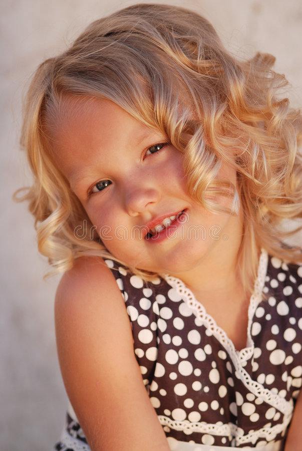 Girl with blond curly hair. Portrait of a cute little girl with blond curly hair royalty free stock images
