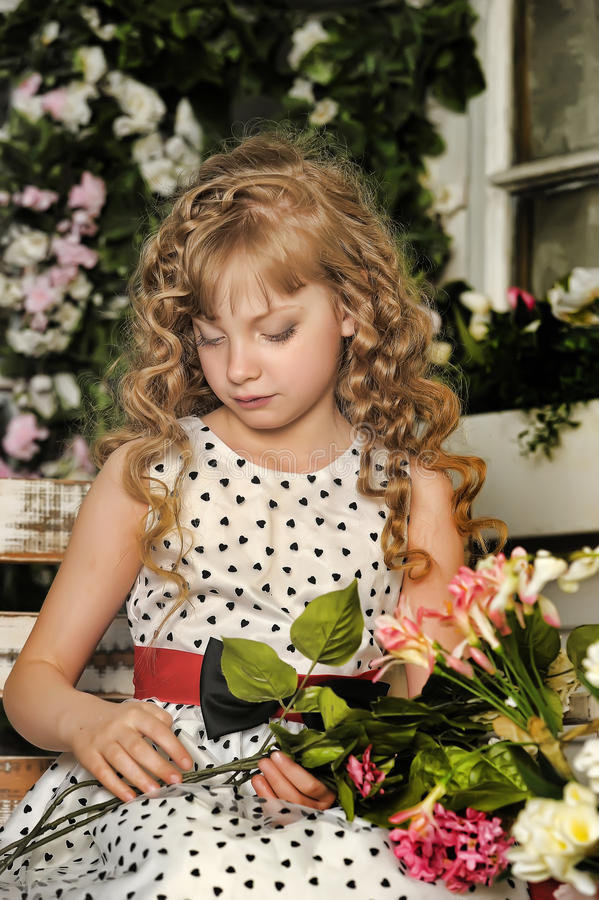 Girl with blond curly hair on a bench with flowers stock images