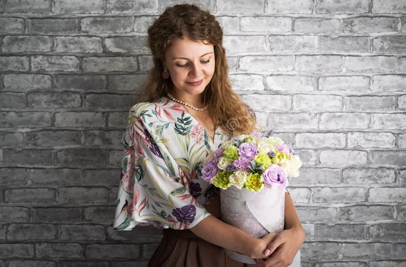 A girl with blond curly hair holds and hugs a large box with flowers against a gray wall. Portrait stock photos