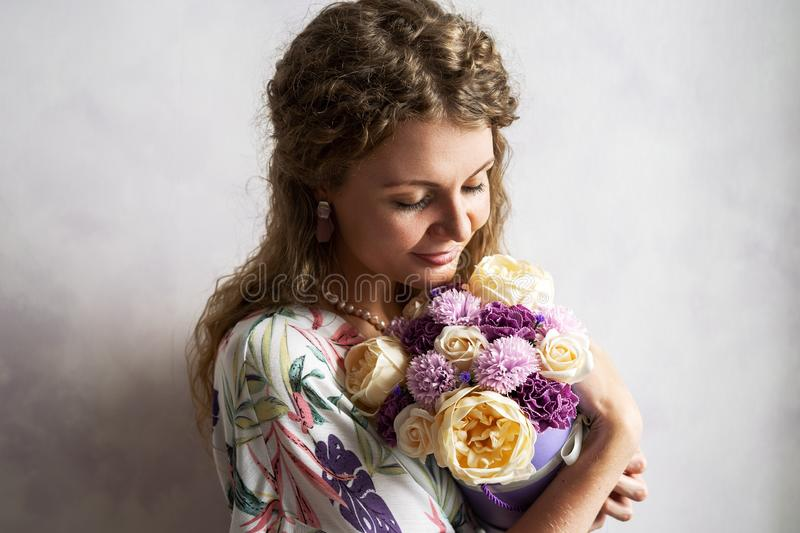 A girl with blond curly hair holds and hugs a large box with flowers against a gray wall. Portrait royalty free stock image