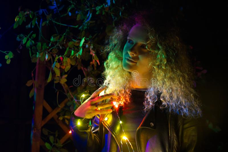 Girl in blond curly hair, illuminated by multi-colored light. stock photography
