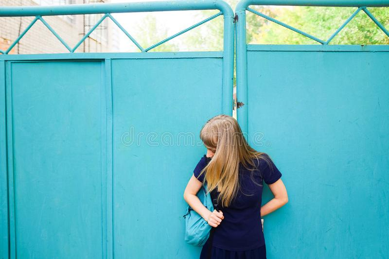 Girl with blond hair, blue Polo shirt, iron gate. The young woman looks down at her backpack. The concept of education, tourism stock images