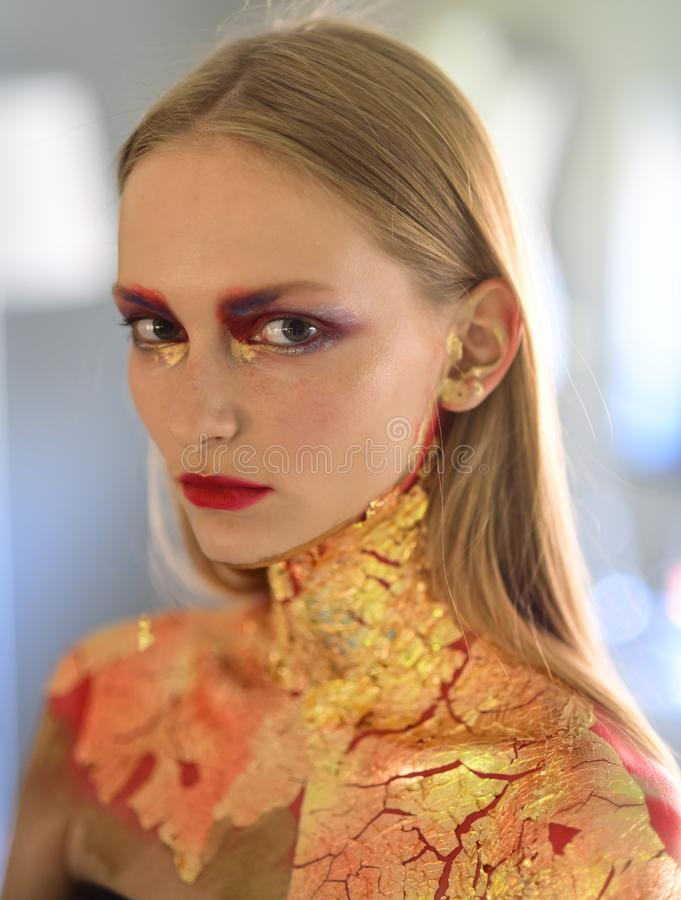 Girl with blond hair, golden foil on skin, cosmetics stock photo