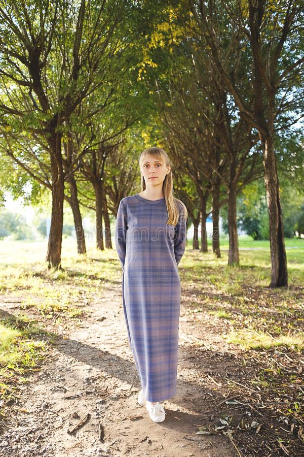 A girl with blond hair, a long striped dress, on a summer day. A young woman with a calm look, looking at the camera, against the royalty free stock photography