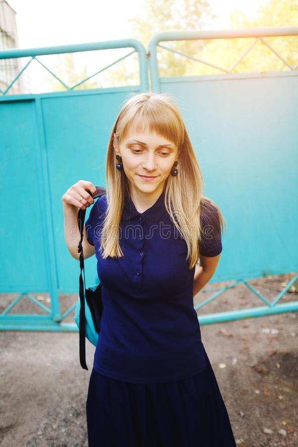 A girl with blond hair, wearing a blue Polo shirt. A young woman, looking down, puts on a backpack against the iron gate. stock image