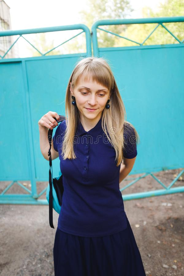 A girl with blond hair, wearing a blue Polo shirt. A young woman, looking down, puts on a backpack against the iron gate. The royalty free stock image