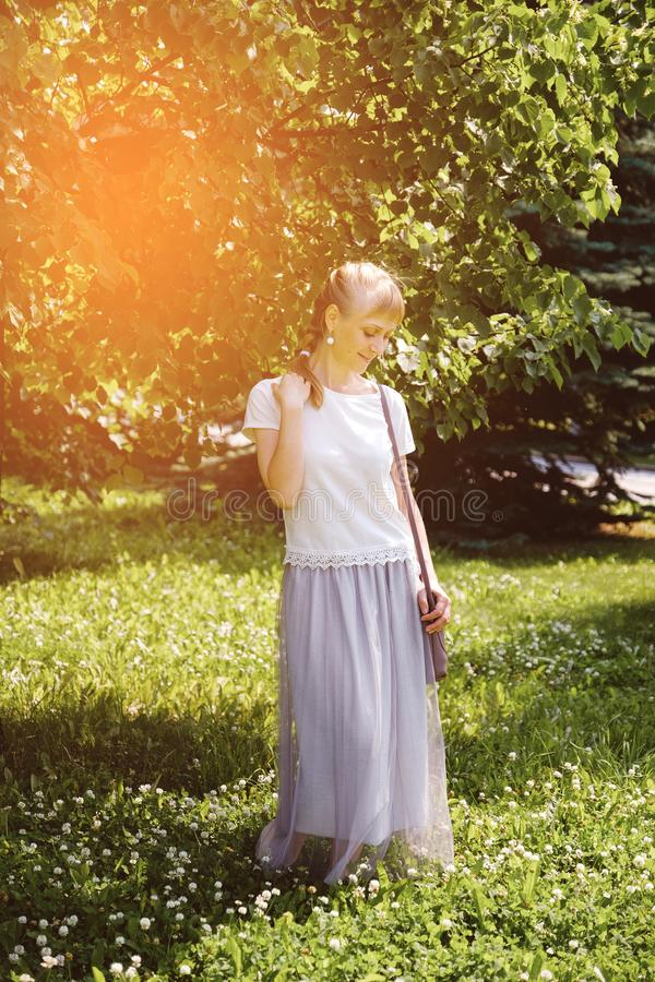 A girl with blond hair, a white t-shirt and a long skirt, on a Sunny summer day. The young woman smiles, looking down stock photography