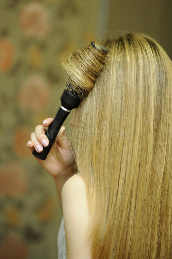 Girl with blond long hair, professional hair styling. Creating an image, barber, hair styling using Brashing royalty free stock photography
