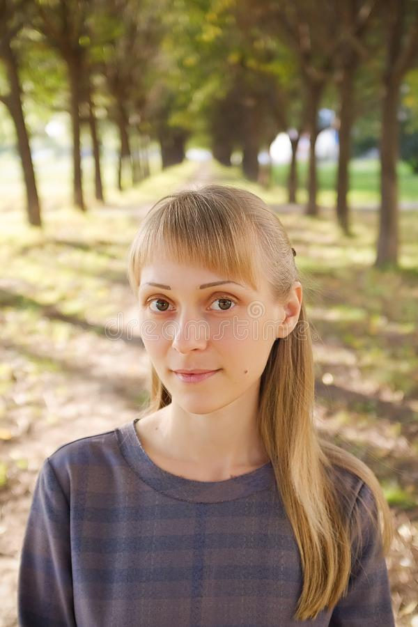 A girl with blonde hair, in a striped dress, on a summer day. A young woman with a calm look, looking at the camera, against the royalty free stock image