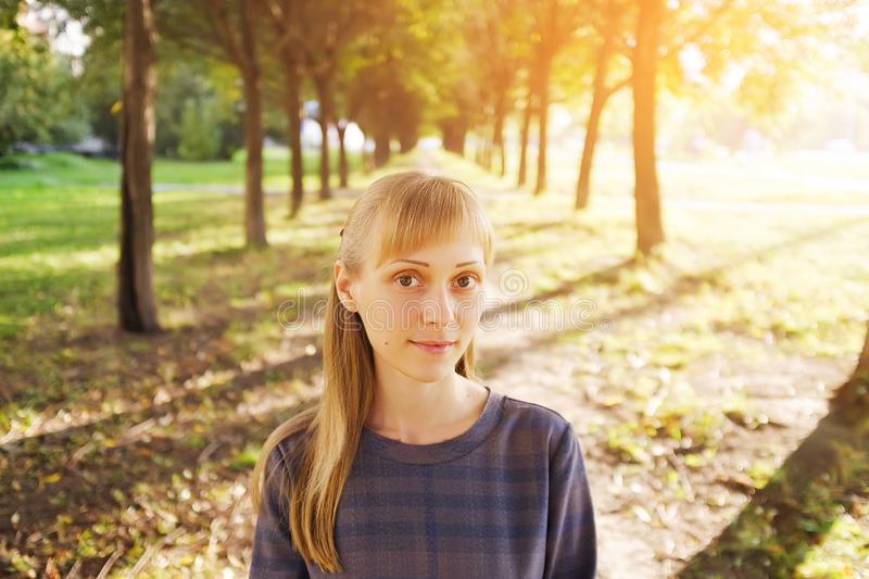 A girl with blonde hair, in a striped dress, on a summer day. A young woman with a calm look, looking at the camera, against the stock photography
