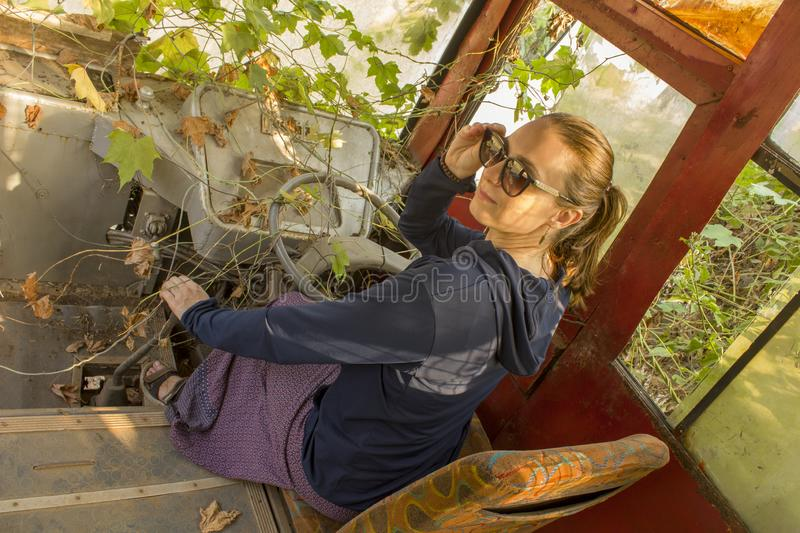 Girl with blonde hair in sunglasses sits and smiles at the driver`s seat in an abandoned ivy-overgrown truck. A girl with blonde hair in sunglasses sits and royalty free stock photography