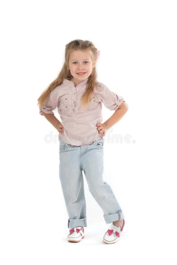 The girl the blonde in a shirt and jeans on wite background. The girl the blonde in a shirt and jeans stands and smiles stock photos