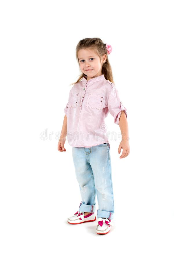 The girl the blonde in a shirt and jeans on wite background. The girl the blonde in a shirt and jeans stands and smile royalty free stock photography