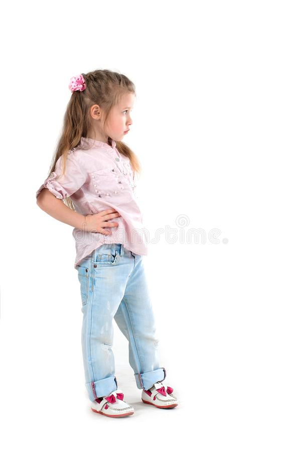 The girl the blonde in a shirt and jeans on wite background. The serious girl the blonde in a shirt and jeans stands and looks aside royalty free stock photos
