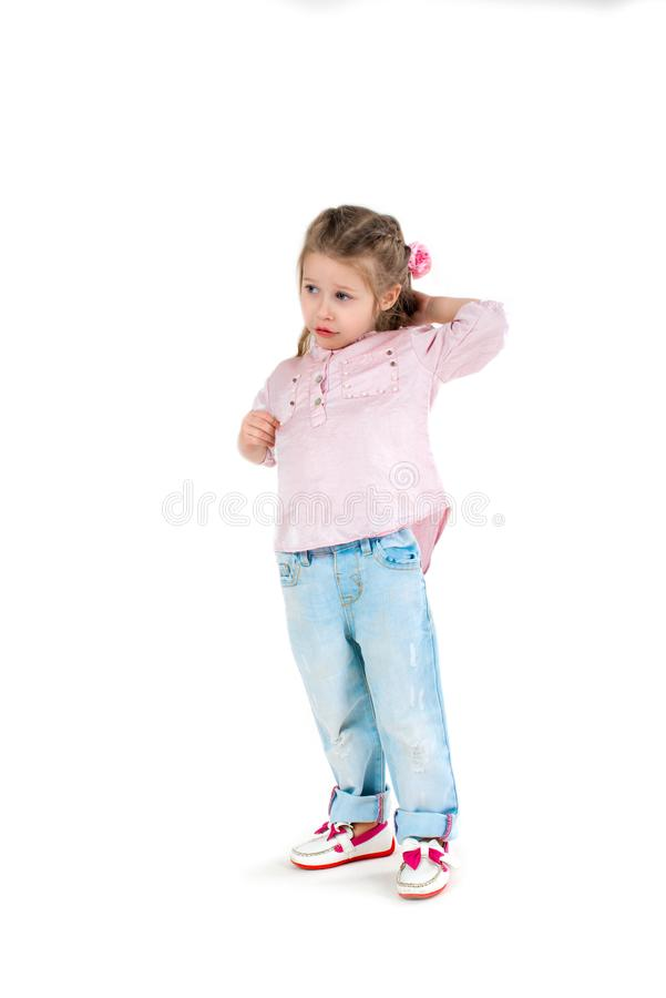 The girl the blonde in a shirt and jeans on wite background. The serious girl the blonde in a shirt and jeans stands and looks aside stock photos
