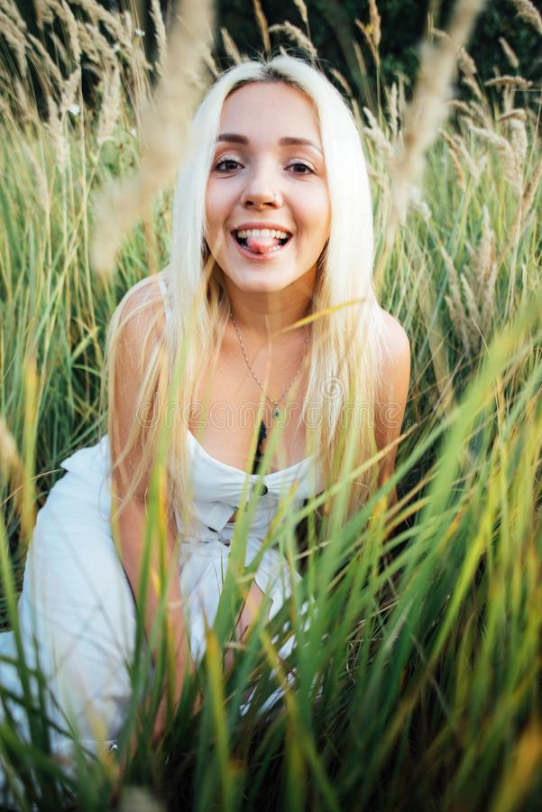 Girl blonde sitting in grass shows tongue fun stock photos