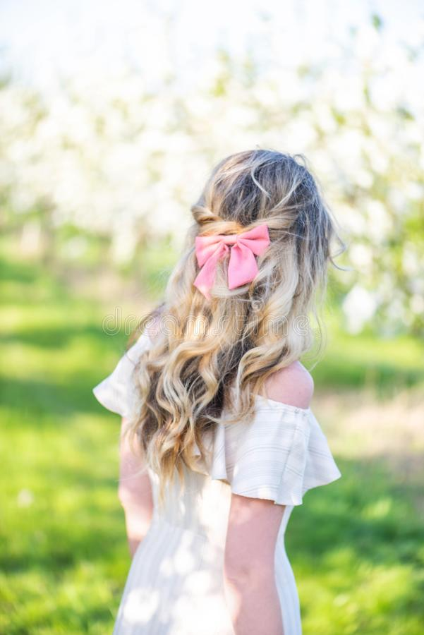 Girl in a blooming orchard at springtime. Seeking or hiding concept. Retro style dress. Colorful springs. Girl in a blooming orchard at springtime. Seeking or royalty free stock photography