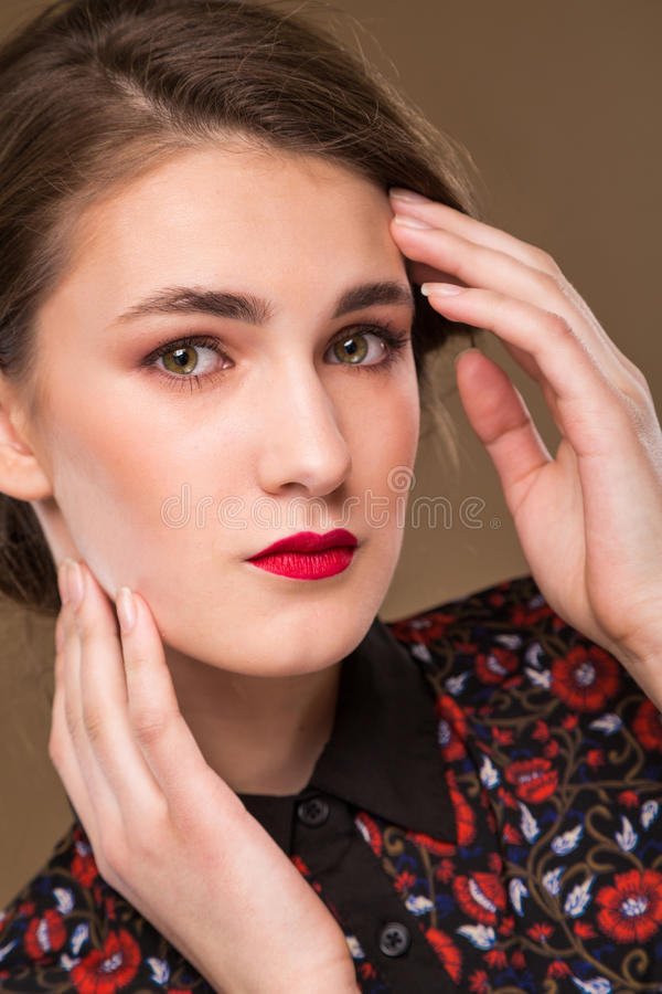 Girl in a blouse. Young girl in a make-up and red lips in dress on a brown background royalty free stock photography