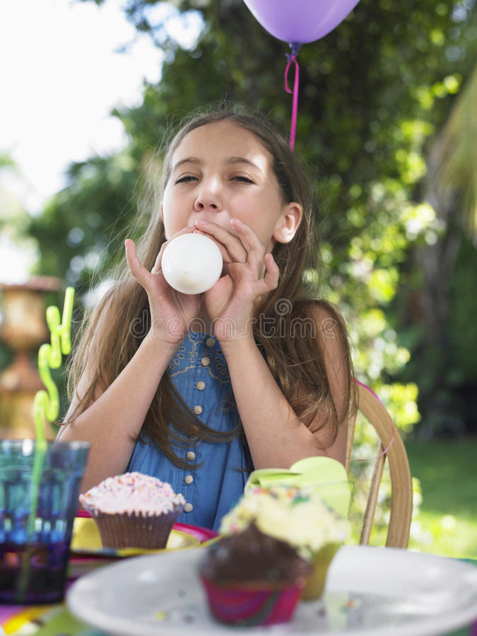 Girl Blowing Balloon At Birthday Party stock photos