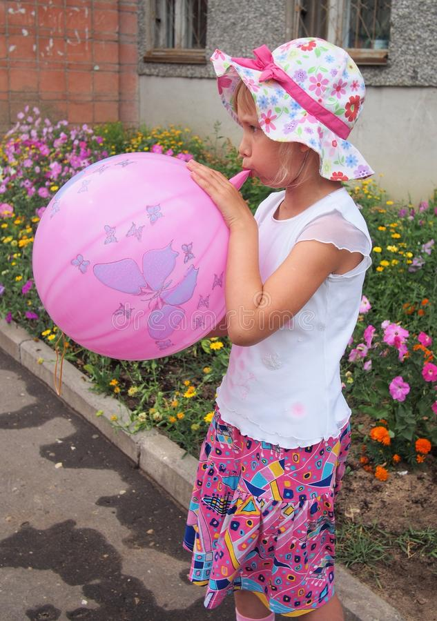 Girl blowing a balloon stock image