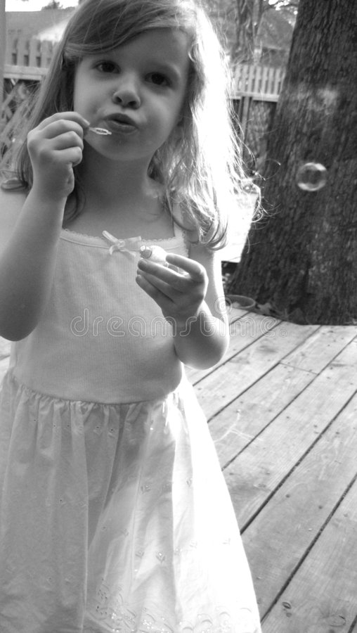 Girl blowing bubbles outdoors stock photography