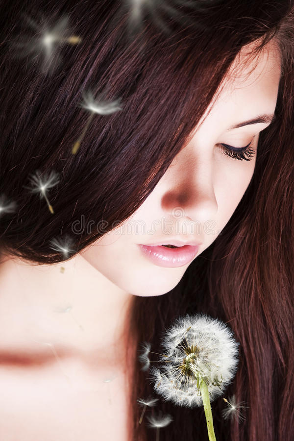 Girl blowing on dandelion. royalty free stock images