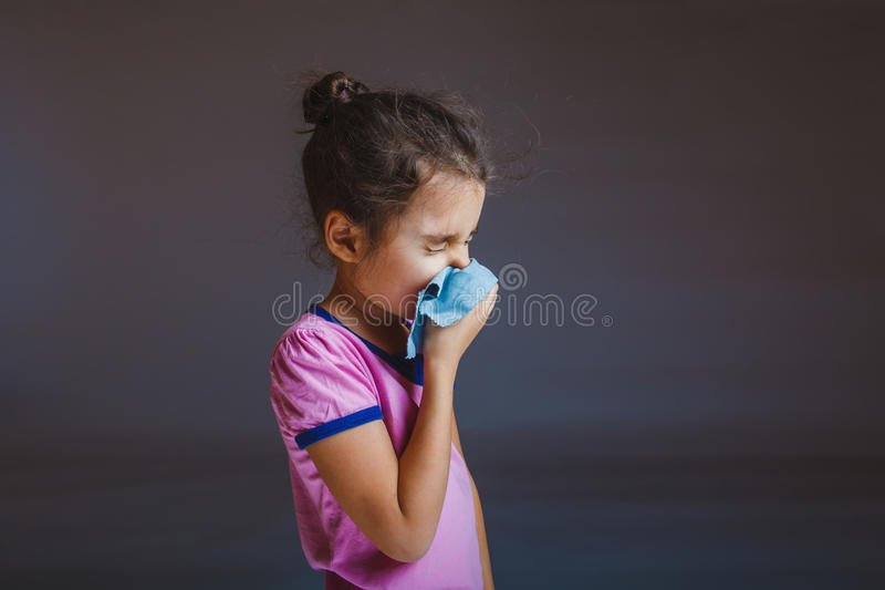 Girl blowing his nose into a handkerchief isolated stock photography