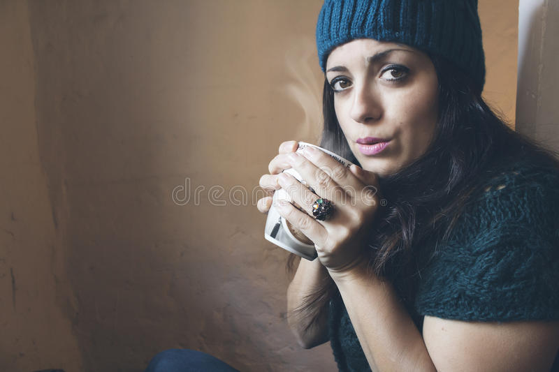 Girl blowing a hot cup royalty free stock photo