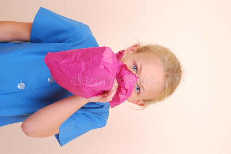 Girl blowing pink paper bag royalty free stock image
