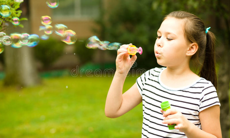 Girl is blowing a soap bubbles royalty free stock image