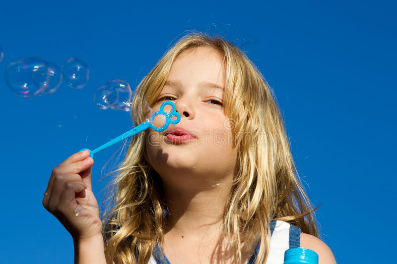 Girl blows bubbles against blue sky stock images