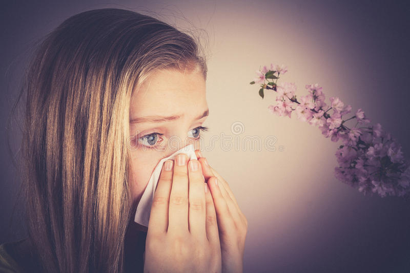 Girl blows her nose, cherry blossoms, grain effect royalty free stock photos