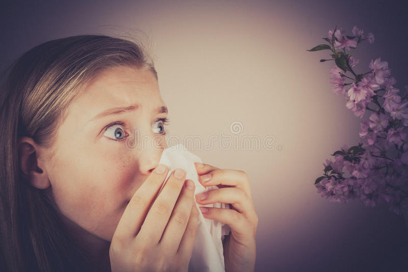 Girl blows her nose with handkerchief, grain effect royalty free stock images