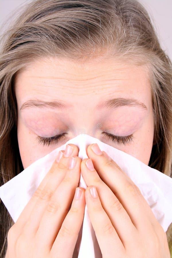 Girl blows her nose with handkerchief, health concept stock photos