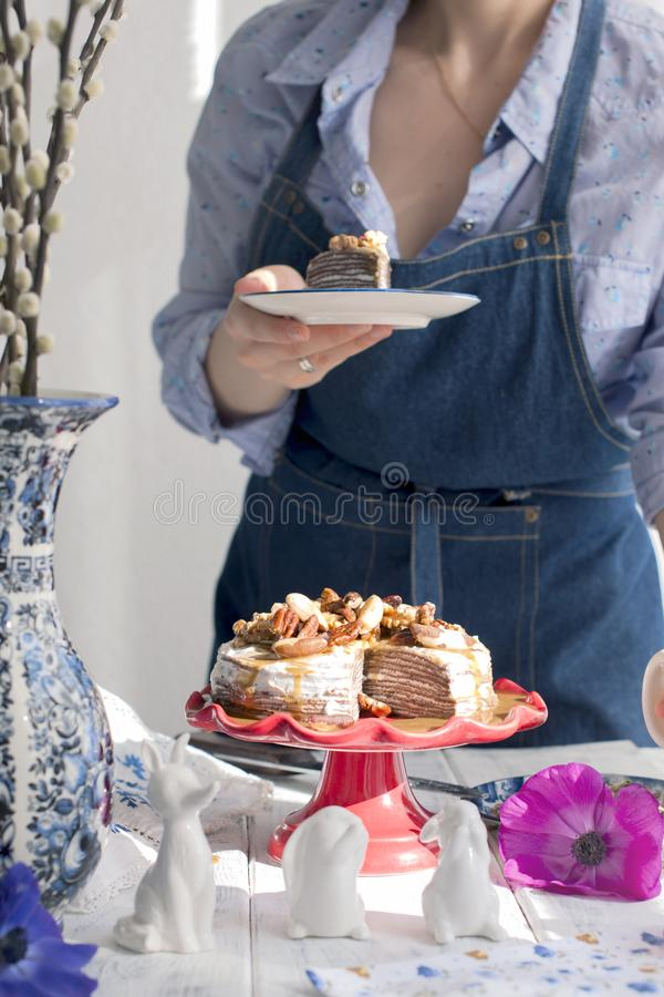 A girl in a blue apron in the kitchen and a cake, flowers in a vase. Light background. royalty free stock image