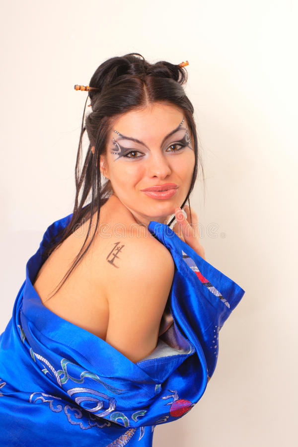 Girl in blue asian bathrobe with dragons. Attractive girl in blue asian bathrobe with dragons royalty free stock photo