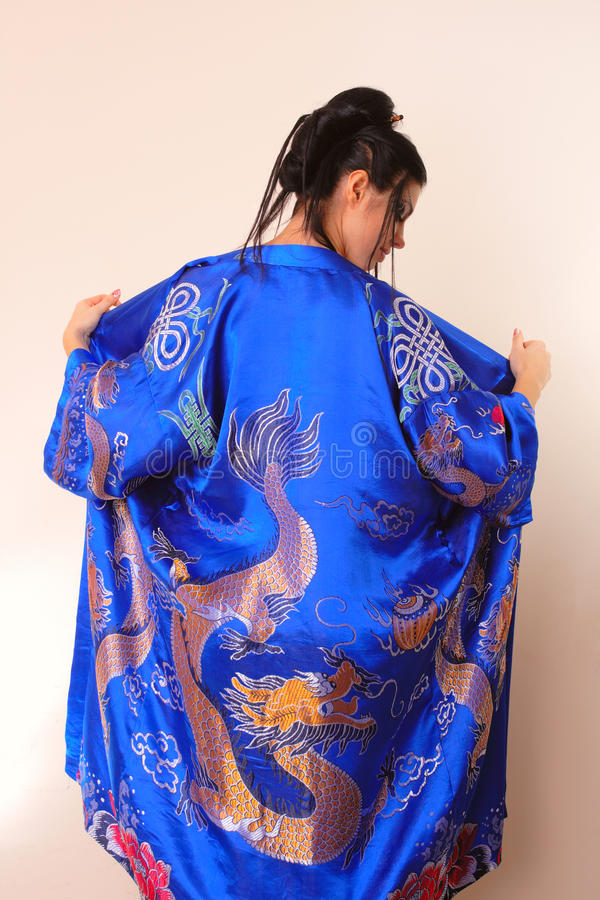 Girl in blue asian bathrobe with dragons. Attractive girl in blue asian bathrobe with dragons stock images