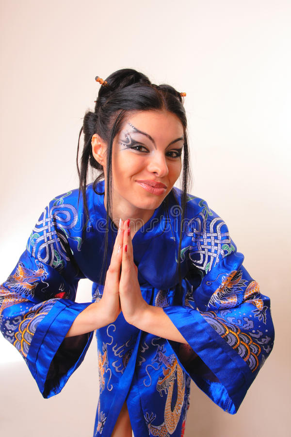 Girl in blue asian bathrobe with dragons. Attractive girl in blue asian bathrobe with dragons royalty free stock photography
