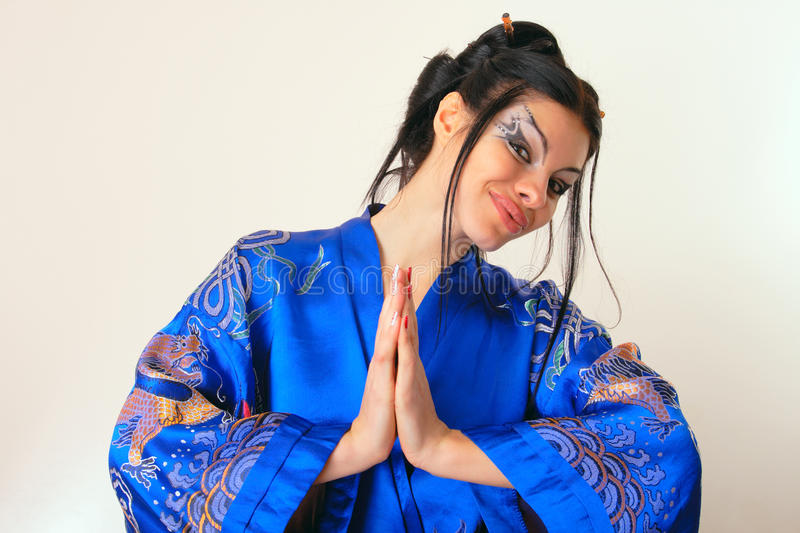 Girl in blue asian bathrobe with dragons. Attractive girl in blue asian bathrobe with dragons stock photo
