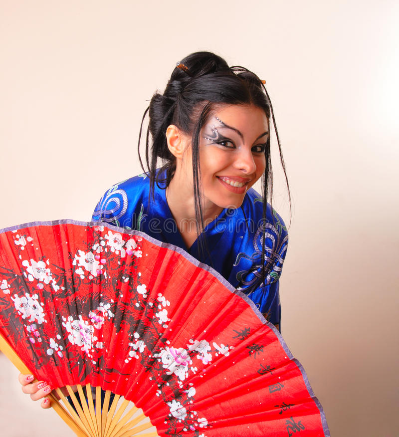Girl in blue asian bathrobe with dragons. Attractive girl in blue asian bathrobe with dragons royalty free stock image