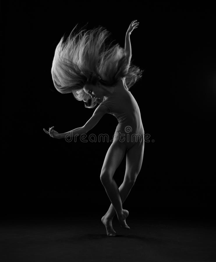 Wave of hair. A girl in blue body with long blond hair makes a swing. Black and white royalty free stock photography