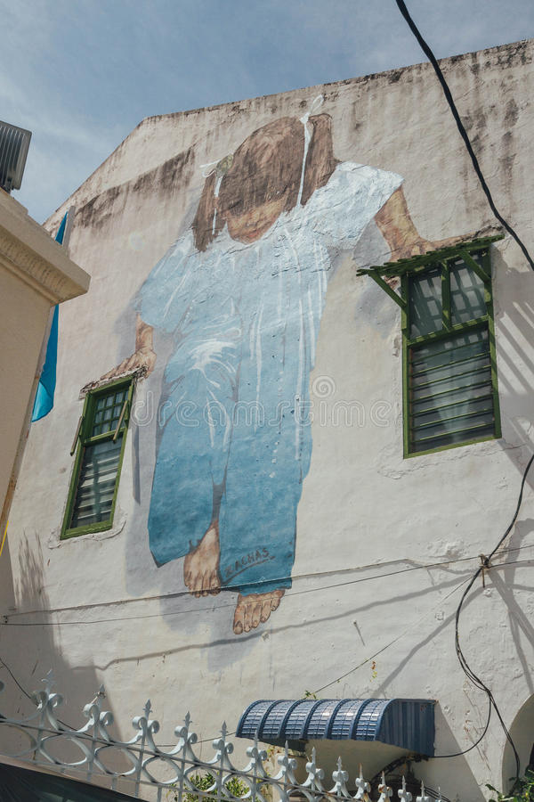 Girl in blue cloth graffitti over the old building in George Town. Penang, Malaysia royalty free stock image